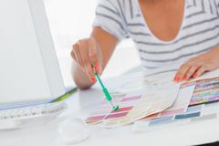 Interior designer pointing at colour charts - stock photo