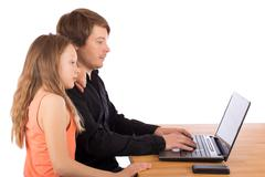 father working with his daughter on a laptop - stock photo