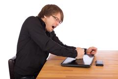 angry man knock with his fist on his laptop - stock photo