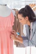 Stock Photo of Pretty fashion designer fixing dress