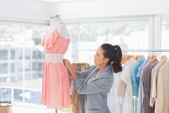 Pretty fashion designer adjusting dress Stock Photos