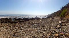 Distant Children On Rocky Pacific Ocean Beach Or Shoreline Stock Footage