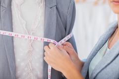 Stock Photo of Fashion designer measuring blazer
