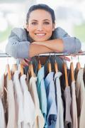 Stock Photo of Pretty fashion designer leaning on clothes