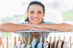 Pretty designer leaning on clothes - stock photo