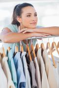 Stock Photo of Fashion designer leaning on clothes rail