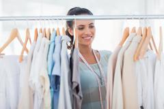 Stock Photo of Attractive fashion designer looking at clothes