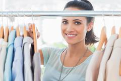 Smiling fashion designer looking at clothes - stock photo