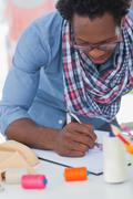 Stock Photo of Fashion designer colouring a draw