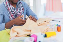Stock Photo of Fashion designer cutting textile