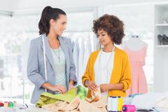 Two cheerful fashion designers touching textile Stock Photos