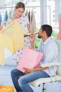 Woman showing clothes to her boyfriend - stock photo