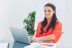 Stock Photo of Cheerful designer working on her laptop