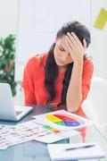 Annoyed designer sitting behind her desk Stock Photos