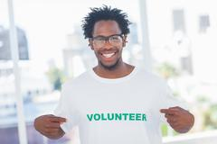 Handsome man pointing to his volunteer tshirt Stock Photos