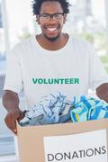 Stock Photo of Cheerful man holding donation box