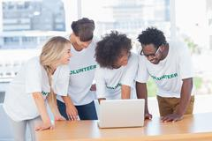 Smiling volunteers working together on a laptop Stock Photos
