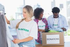 Volunteers putting clothes in clothes rail - stock photo