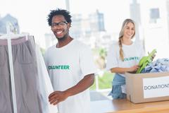 Stock Photo of Pretty volunteers taking clothes out of a donation box