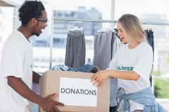Stock Photo of Cheerful volunteers looking at a donation box