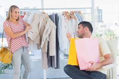 Stock Photo of Depressed man looking at his shopaholic girlfriend