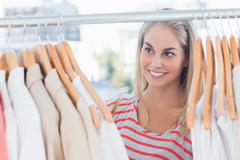 Pretty woman looking at clothes - stock photo