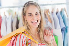 Stock Photo of Cheerful woman standing in a clothing store