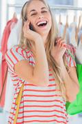 Blonde woman laughing in a clothing store - stock photo