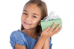 Stock Photo of Smiling girl excited while holding a present