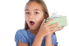Stock Photo of Smiling girl astonished while holding a present