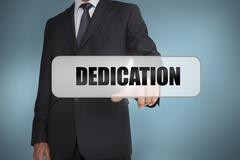 Businessman selecting the word dedication written on white tag - stock photo