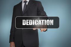 Businessman touching the word dedication written on black tag - stock photo