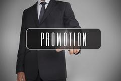 Businessman selecting label with promotion written on it - stock photo