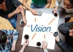 Team brainstorming over a poster with vision written on it Stock Photos
