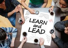 Stock Photo of Learn and lead written on a poster with drawings of charts