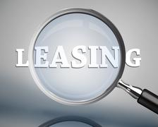 Magnifying glass showing leasing word in white Stock Photos