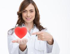 Doctor holding and pointing at a red heart Stock Photos