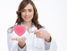 Doctor holding and pointing at a pink heart - stock photo