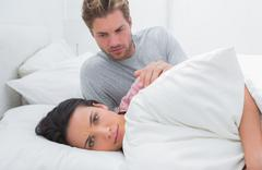 Sad woman ignoring her partner in her bed Stock Photos
