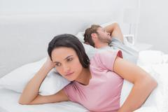 Woman annoyed that her partner is sleeping - stock photo