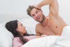 Stock Photo of Shirtless man posing next to his sleeping partner