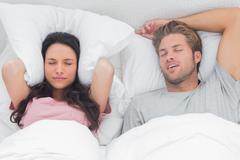 Stock Photo of Woman annoyed by the snoring of her partner
