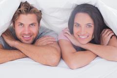 Couple smiling under the duvet Stock Photos