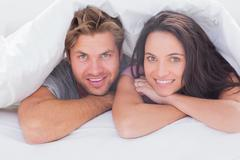 Cheerful couple under the duvet - stock photo