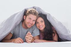 Beautiful couple under the quilt Stock Photos