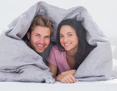 Cheerful couple wrapped in the duvet Stock Photos
