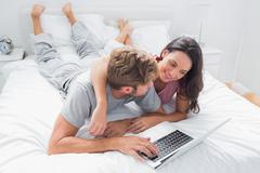 Pretty woman embracing her husband in bed - stock photo