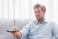 Man changing tv channel sat on the couch Stock Photos