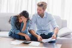 Worried couple doing their accounts - stock photo