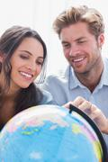 Happy couple looking at a globe - stock photo